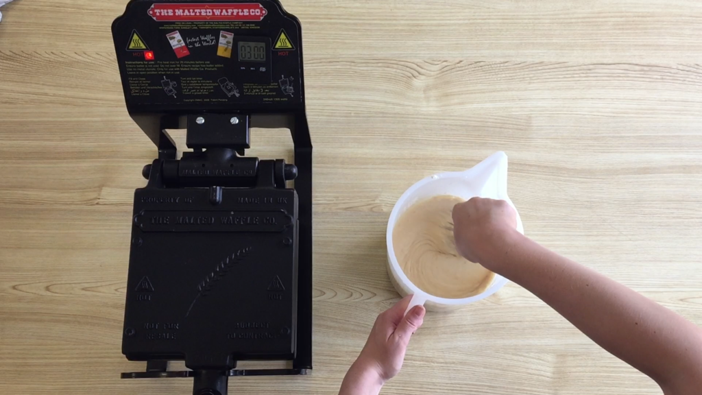 Someone mixing waffle batter.